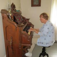 "Virginia provided music on the old pump organ.  Although she proclaimed, ""I'm not good"", she demonstrated considerable prowress at the organ and entertained us with several songs"