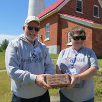 Al and Alma hold a brick donated by Jerry Waters and Marie Vincent.  The brick will be placed in a walkway at Tawas Point