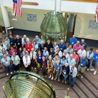 Group photo among the wonderful lenses at the ATON Museum at the Coast Guard Training Center in Yorktown.