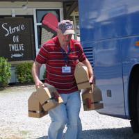 Always helpful, the head Bag Boy, Norm, is seen here carrying lunches to a hungry crowd on the coach.