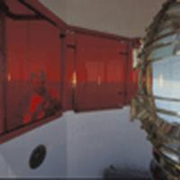 The lens caught with the light bulb lighted and showing the red sectors that warn boaters of the shoal hazard zones.
