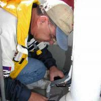 Cullen Chambers, lead preservationist, scrapes base of lens pedestal to determine original color.