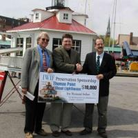 George Layfield, Chief of Staff of the Injured Worker's Insurance Fund (IWIF) presents a check for $10,000 to Henry Gonzalez, U.S. Lighthouse Society, and Buck Buchanan, Annapolis Maritime Museum. IWIF is the first corporate sponsor for the lighthouse partnership.