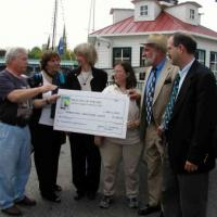 Mr. Jerry Siatkowski, President of the Beacons of the Bay lighthouse collectible club presents a donation check for $1,000 to Mayor Moyer; Secretary Norton; Anne Puppa, Vice President for Preservation, Chesapeake Chapter; Wayne Wheeler, U.S. Lighthouse Society; and Henry Gonzalez, U.S. Lighthouse Society.